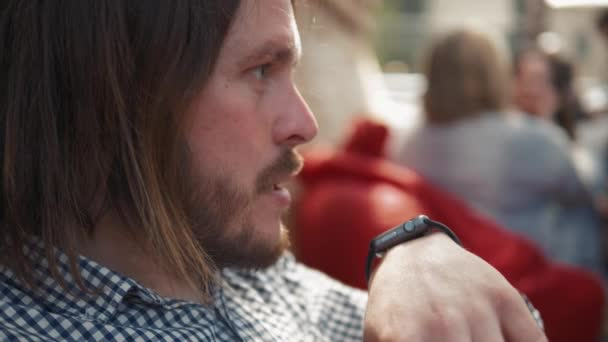 Photo Man with smartwatch using voice recorder recognition audio message command outside on street. Deadline, technology and people concept - creative man with smartwatch using voice command recorder