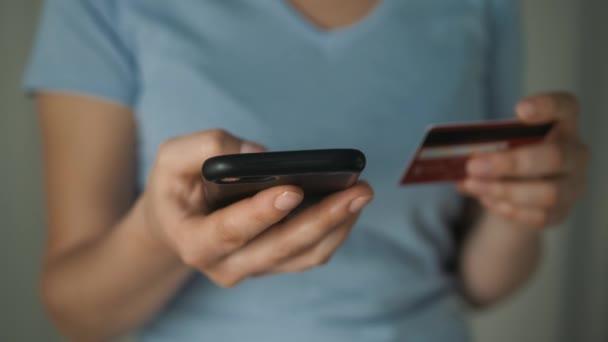 Közelről Womans kezében a hitelkártya és a mobiltelefon használata az online vásárlás