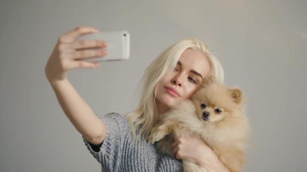 Krásná blondýnka žena dělat selfie s její spitz izolované na šedé, student dívka model pózovat s maskou aplikace s domácím mazlíčkem
