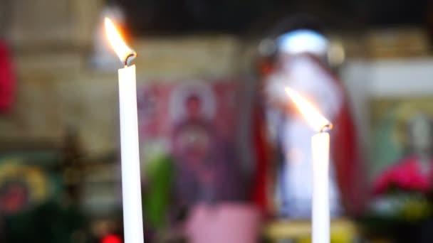 zwei brennende lange weiße Kerzen in der Nähe von Ikonen