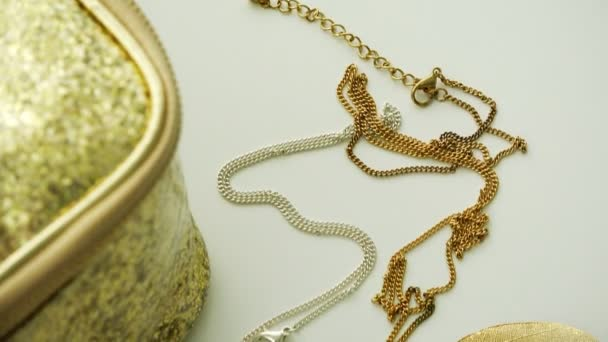 gold jewelry on a chain on white background