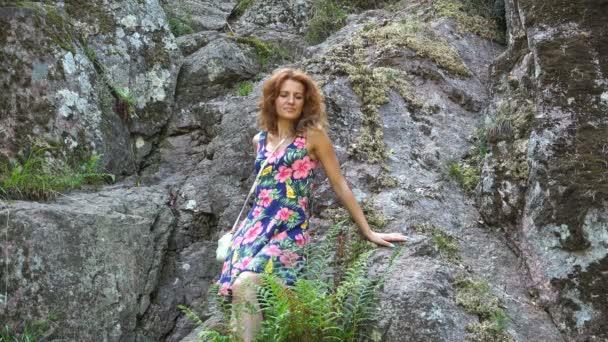 lány nyári ruhában pózol a kamera sziklák
