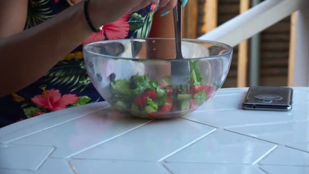 girl at the table eats vegetable salad from glass tableware