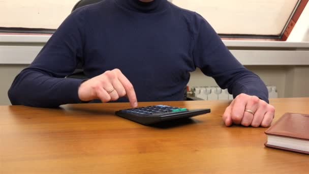 A man counts on a calculator and rubs his palms