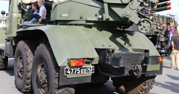 children are sitting in combat vehicles. Museum exhibit of military equipment