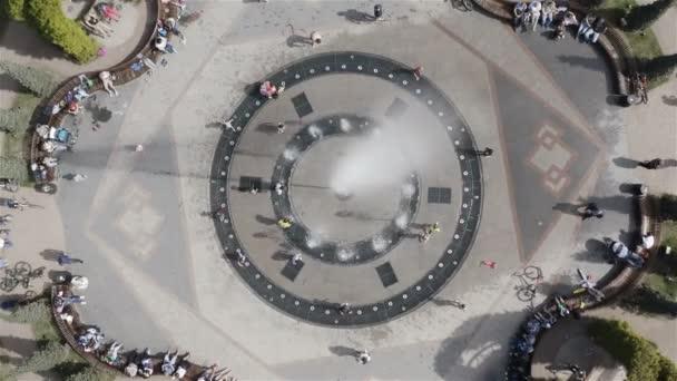 Kinder und Erwachsene planschen im Wasser des Brunnens an einem heißen sonnigen Tag