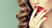 Photo Beautiful girl with long wavy hair . woman with red manicure . girl with bright color nail polish on the nails . Makeup and cosmetics
