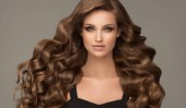 Photo Brunette girl with long and shiny curly hair. Beautiful model woman with wavy hairstyle. Care, cosmetics and beauty