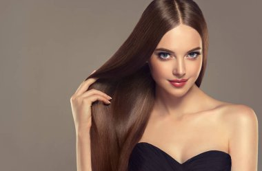Beautiful model girl with shiny brown and straight long hair . Keratin straightening . Treatment, care and spa procedures. Medium length hairstyle.