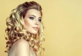 szőke lány hosszú, fényes göndör haj. Gyönyörű modell nő göndör frizura. És kozmetikai