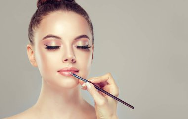 Makeup artist applies pink gloss lipstick . Beautiful woman face. Hand of make-up master, painting lips of young beauty model girl . Make up in process
