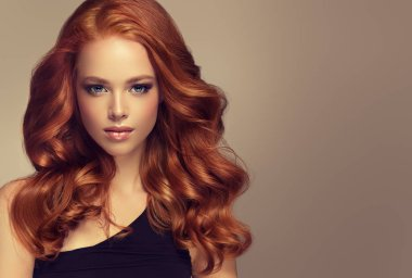 Young, red haired woman with voluminous hair.Beautiful model with long, dense, curly hairstyle