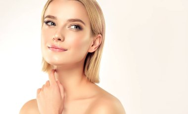 Beautiful Young Woman with Clean Fresh Skin . Facial treatment . Cosmetology , beauty and spa . Blonde girl with short hair and a clean face