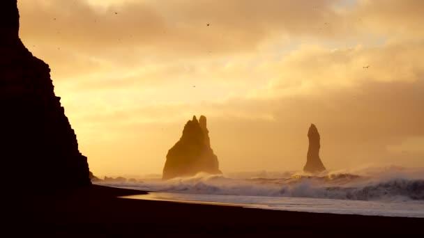 Hullámok összeomlik a szikla a fekete strand Izland