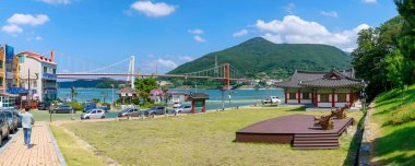Namhae, South Korea - July 29, 2018 : Chungnyeolsa shrine garden with Namhae Bridge and Yi Sun-sin turtle ship in Namhae County, South Gyeongsang Province