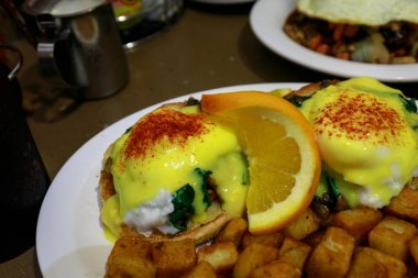Eggs Benedict - Traditional American breakfast with potato salad