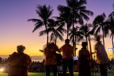 Honolulu, Hawaii - Dec 23, 2018 : Tropical colorful sunset with Orchestra and palm trees silhouette in Waikiki beach