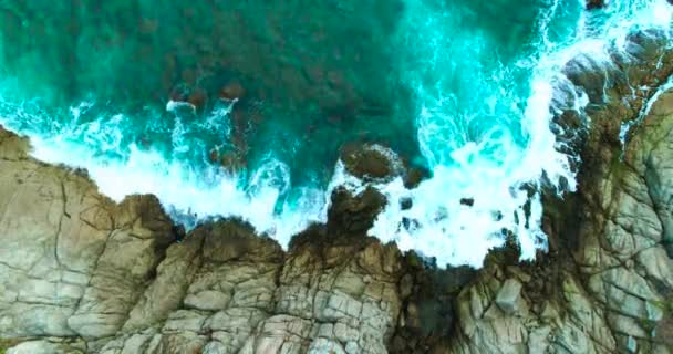 Aerial: Sea waves are washing up big rocks.