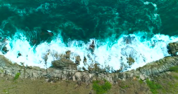 Aerial: Ocean waves are washing up big rocks on the sea rocky coast.