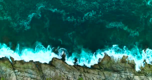 Aerial: The sea waves break against the rocks on the shore.