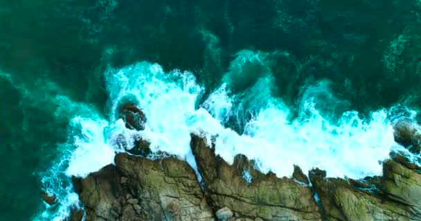 Aerial: Beautiful ocean waves with white foam on rocky coastline.