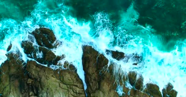 Aerial: Beautiful sea waves with white foam on rocky coastline.