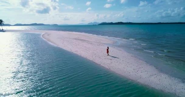 Anténa: Dívka v červených šatech na bílý písek