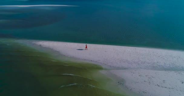 Letecká: Dívka v červených šatech chodí na pláži s bílým pískem