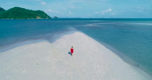 Aerial: A brunette girl in the red dress walks on the white sand beach.