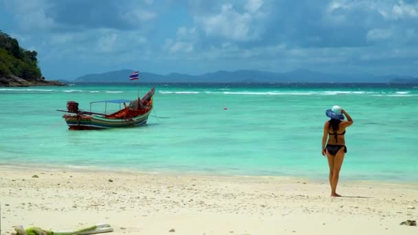 A girl is standing on the beach and looking at a traditional Thai longtail boat.