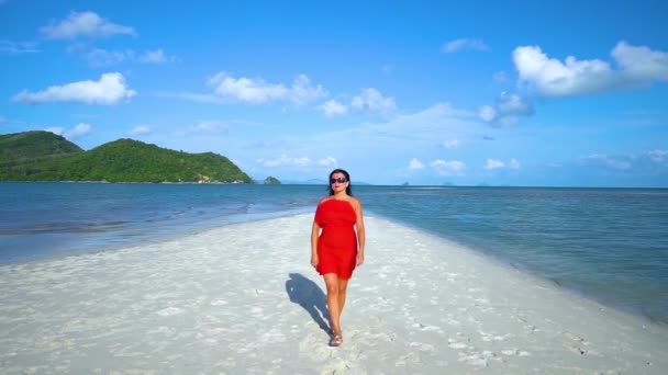 A brunette girl in the red dress walks on the white sand beach.