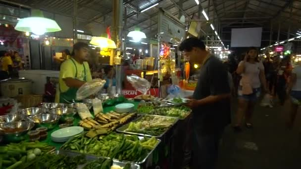 PHUKET, THAILAND September 9, 2018: An Asian night market. The buyer buys vegetables from the seller.