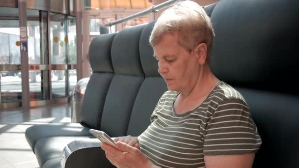 Seniorin hält modernes Smartphone im Einkaufszentrum vor Drehtüren. Konzept für ältere Menschen und moderne Technik