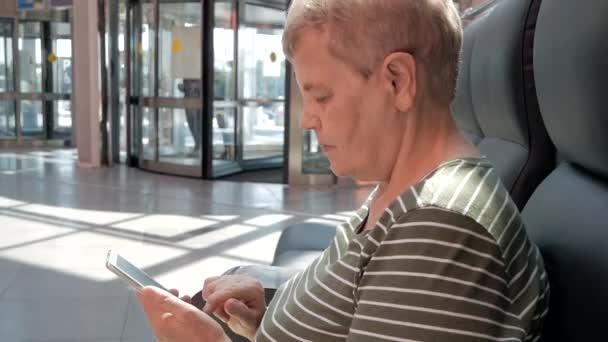Nahaufnahme von senior Frau halten und mit modernen Smartphone in Business-Shopping-Center vor Drehtüren. Konzept der älteren Menschen und moderner Technik