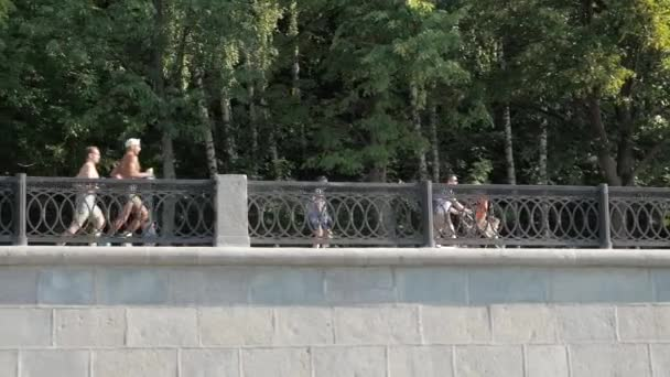 Panning shot of beautiful embankment with people walking, jogging, doing sport and relaxing