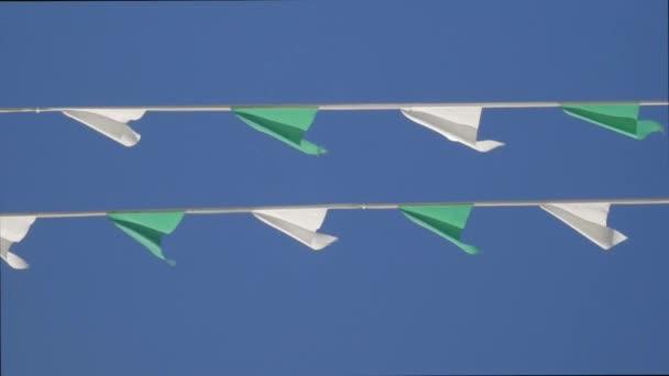 Zöld és fehér sármány ünnepi zászlók mozgó ellen, blue sky vonalak