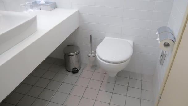 Interiér zrekonstruovaný moderní prostornou koupelnu s bílými dlaždicemi, splachovací záchod a velké umyvadlo