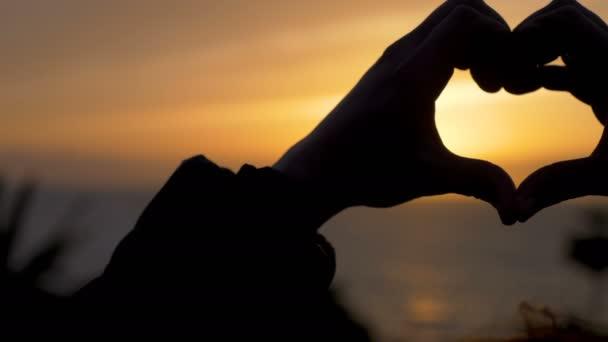 Tvar srdce dělat rukama při západu slunce - zblízka