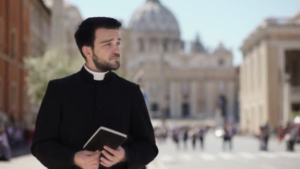Porträt eines jungen katholischen Priesters scrollt die Bibel und das Lächeln in die Kamera