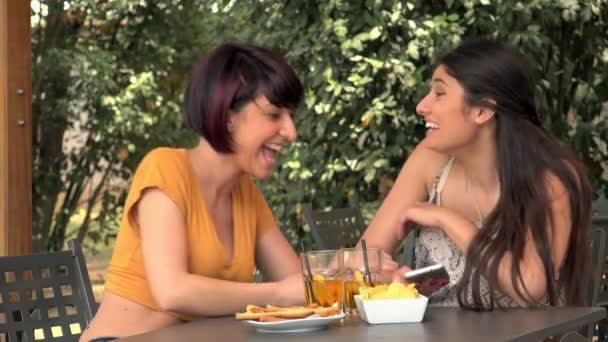 Two Girlfriends Using Smart Phone While Sitting In A Cafe Outdoors