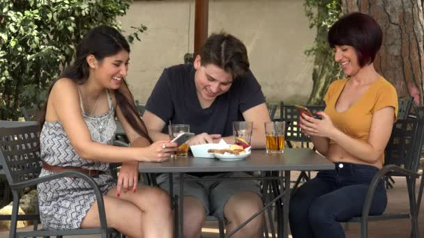 Three Friends With Smartphones Drinking At Bar