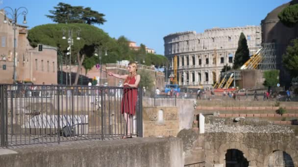 beautiful and elegant tourist takes selfie under the colosseum