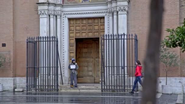 Porträt einer jungen Frau mit roter Jacke spendet einem Bettler am Eingang der Kirche Almosen