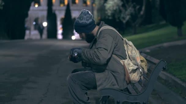 Obdachlose spazieren nachts durch den Stadtpark und zählen sein Almosen