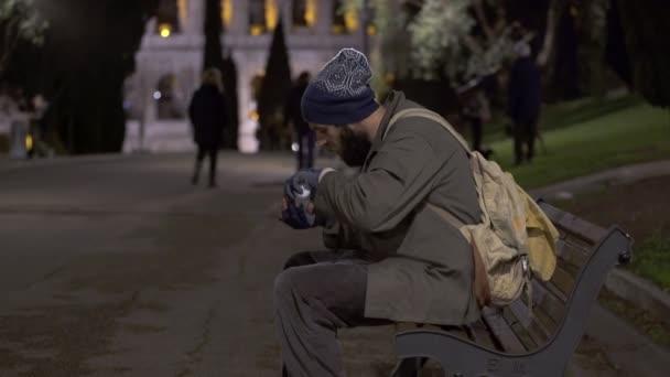 einsamer Bettler sitzt nachts auf Bank und jubelt über sein Almosen