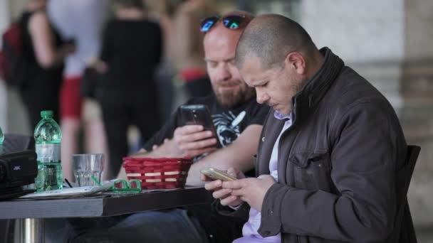 dva přátelé sedí v restauraci používají smartphony