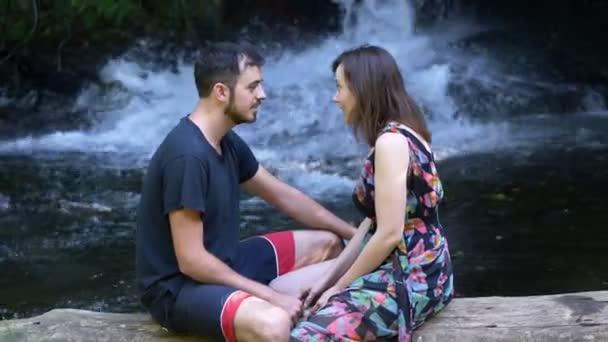 portrét milenců na kmen stromu-vodopád pozadí