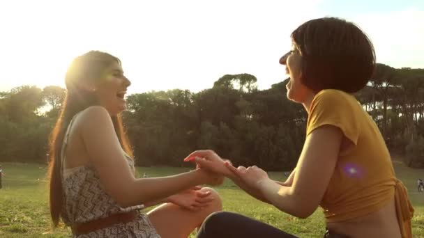 portrait of laughter and talk among women at sunset- friends laugh and joke at the park