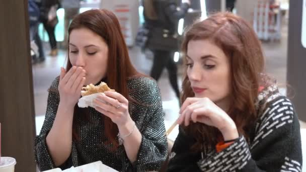 Hungry pensive young women eating at fast food