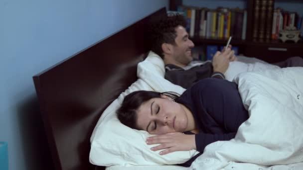 Krize manželství: manžel si hraje s smartphone v posteli, jeho žena naštve